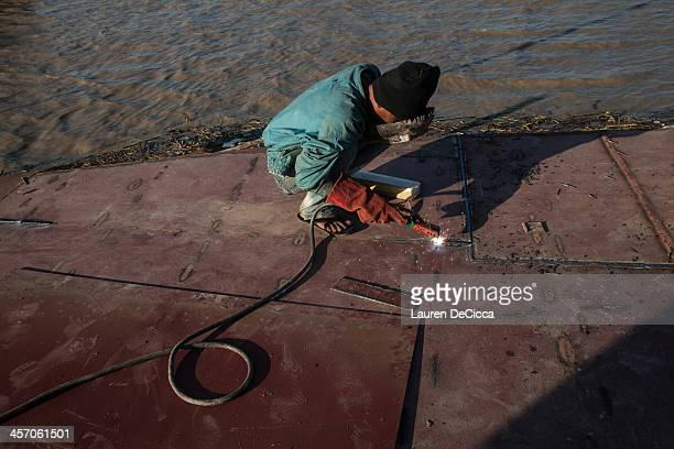A man works to repair a cargo ship on the banks of the Irrawaddy River on December 16 2013 in Yangon Myanmar Large cargo ships on the Irrawaddy River...