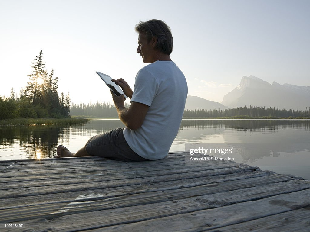 Man works with ipad on wharf, mountain lake : Stock Photo