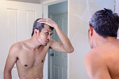 Man worried about gray hair while looking into a mirror.