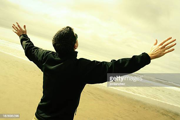 A man worshipping with his hands in the air on a beach