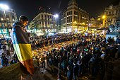 TOPSHOT A man wrapped in a Belgian flag holds a candle as people gather at a makeshift memorial in front of Brussel's Stock Exchange on Place de la...