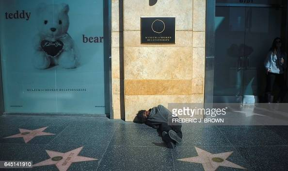 A man wrapped in a blanket sleeps on the Walk of Fame sidewalk in front of the Museum of Broken Relations in Hollywood California on February 22 a...