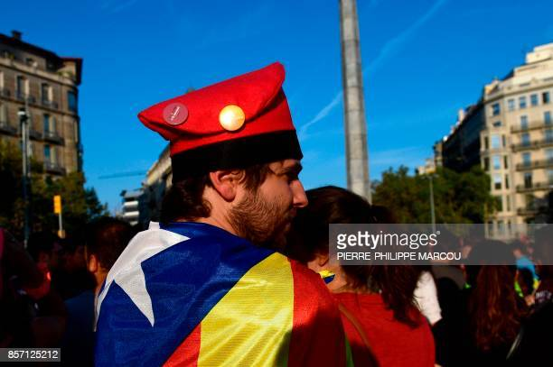 A man wrapped in a Catalan proindependence 'Estelada' flag and wearing a barretina hat attends a demonstration called by the General Confederation of...