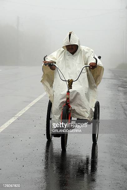 A man wrapped in a plastic poncho rides his tricycle along the Panamerican highway under the rain 30 km south of Tegucigalpa on October 15 2011...