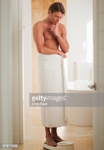 Man wrapped in a towel standing on bathroom scale : Stock Photo