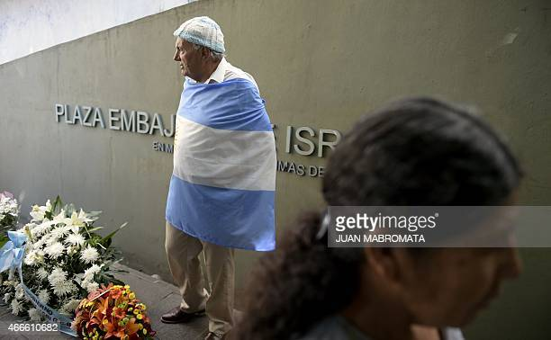 A man wrapped in an Argentine flag waits for the beginning of the ceremony to commemorate the 23rd anniversary of the bombing against the Israeli...