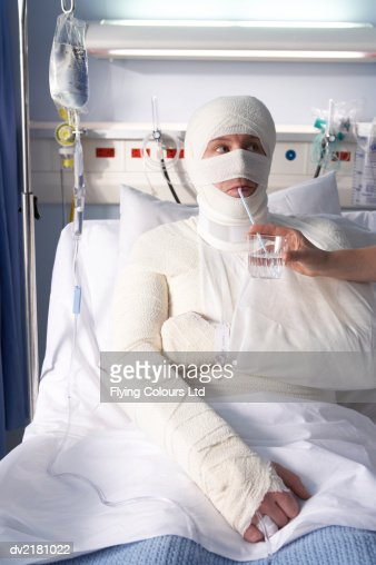 Man Wrapped in Bandages Drinking Water From A Straw
