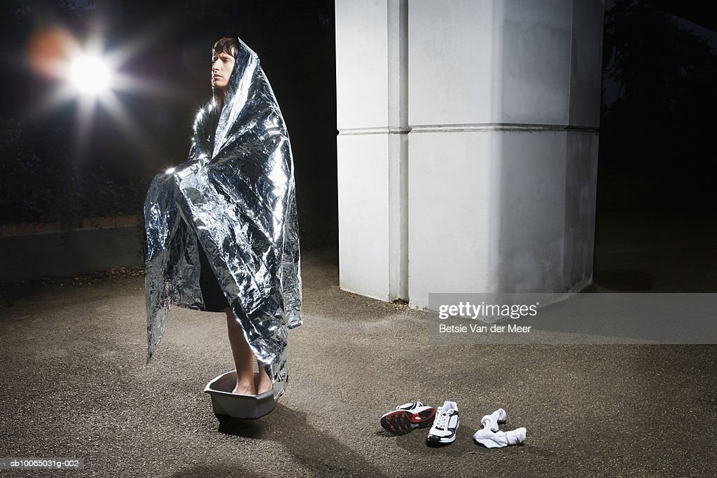 Man wrapped in blanket standing in bucket, looking away : Stock Photo