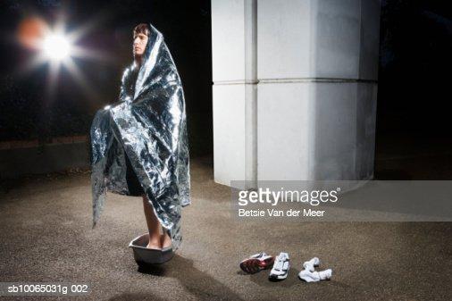 Man wrapped in blanket standing in bucket, looking away : Stock Photo
