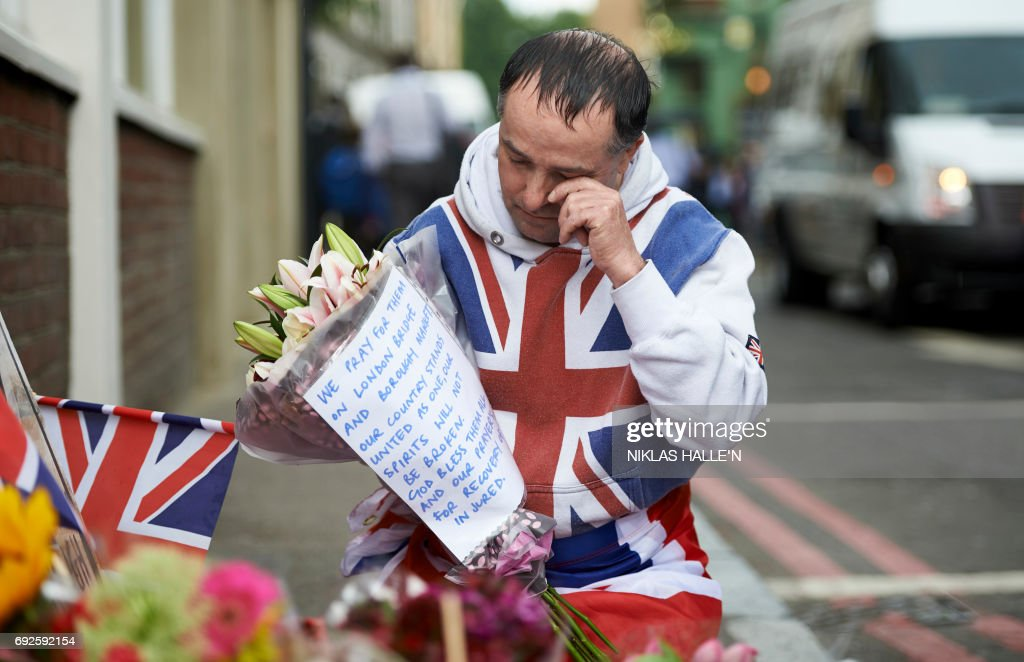 TOPSHOT - A man wrapped in Britain's Union Flag prepares to lay flowers at a police cordon on Borough High Street, near Borough Market, in London on June 5, 2017 in tribute to the victims of the June 3 terror attack on London Bridge and at the market. Police carried out fresh raids and arrested 'a number of people' on Monday after the Islamic State group claimed an attack by three men who mowed down and stabbed revellers in London on June 3, killing seven people, before being shot dead by officers. / AFP PHOTO / NIKLAS HALLE'N