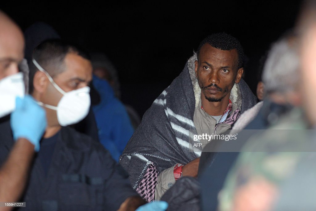 A man wrapped up in a blanked stang after being rescued and brought ashore to the Armed Forces of Malta Maritime base, on November 9, 2012 in Valletta. The Maltese military rescued 250 undocumented migrants believed to be Eritrean from a stricken boat, officials said, after reports the vessel had been adrift for days. AFP PHOTO/Matthew Mirabelli -MALTA