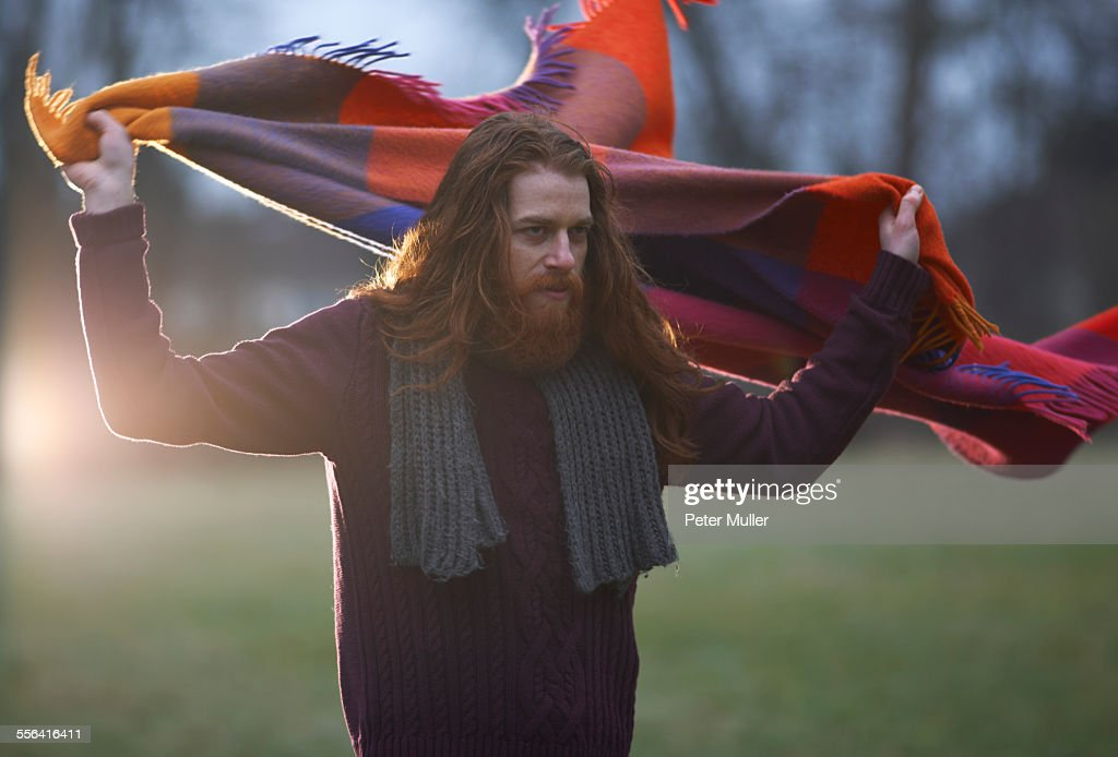 Man wrapping blanket around himself in countryside
