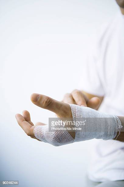 Man wrapping hand with gauze, cropped view