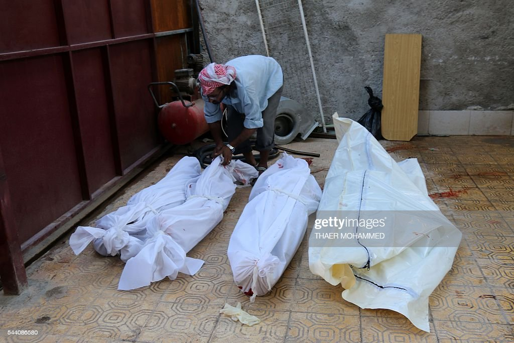 A man wraps bodies in shrouds following a reported airstrike at a market in the rebel-held district of Tariq al-Bab, in the northern city of Aleppo on July 1, 2016. Separate air raids in northern Syria by regime aircraft and warplanes of the US-led international coalition killed at least 25 civilians, a monitoring group said. President Bashar al-Assad's air force attacked a crowded market in Aleppo city's rebel-held district of Tariq al-Bab, killing 11 people, the Syrian Observatory for Human Rights reported. MOHAMMED
