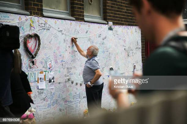 A man writes a message on the ever growing message board of condolences near the tower June 16th 2017 London United Kingdom Grenfell Tower burned out...