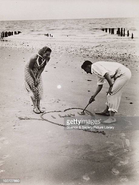Man writes 'I LOVE U' in the sand for his sweetheart 192060 Photographic archive of Photographic Advertising Limited Comprising stock sheets...