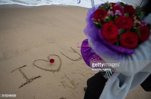 A man writes 'I love U'on the beach for his girlfriend on February 14 2016 in XiamenChina Valentine's Day also known as Saint Valentine's Day or the...