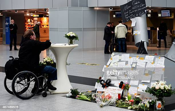 A man writes in a condolence book for the victims of the Germanwings plane crash in the departure area of the airport Duesseldorf western Germany on...