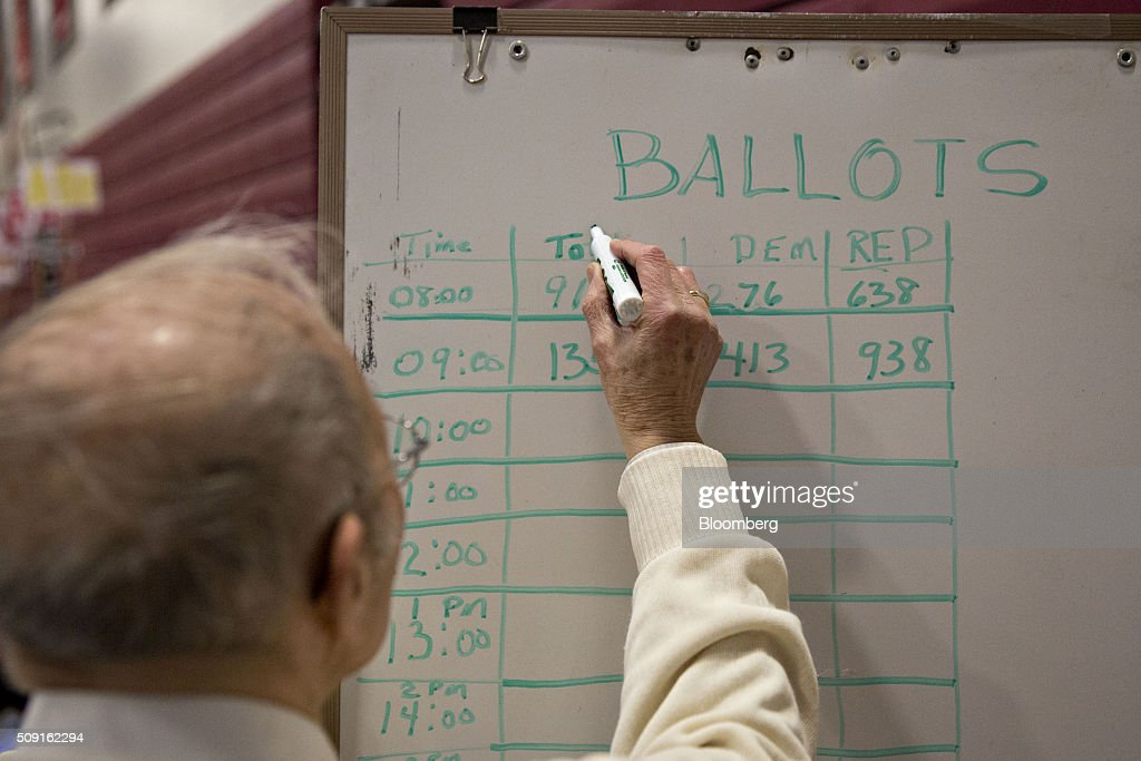 A man writes on a board recording democratic and republican vote totals at a polling station in Bedford, New Hampshire, U.S., on Tuesday, Feb. 9, 2016. Voters in New Hampshire took to the polls today in the nations first primary in the U.S. presidential race. Photographer: Daniel Acker/Bloomberg via Getty Images