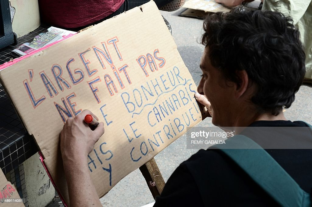 A man writes on a cardboard ''Money doesn't make you happy but cannabis contributes to it'' during a protest to call for the legalization of marijuana on May 10, 2014 in Toulouse, southern France. About 147 million people globally -- or about 2.5 percent of the population -- use cannabis, according to the World Health Organization. GABALDA