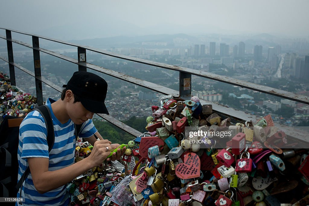 A man writes on a padlock as he leaves it on a fence with others, before the Seoul city skyline during heavy rain on July 2, 2013. July marks the wet season for Seoul during which the city of10 million people receives some 60 percent of its annual rainfall. AFP PHOTO / Ed Jones
