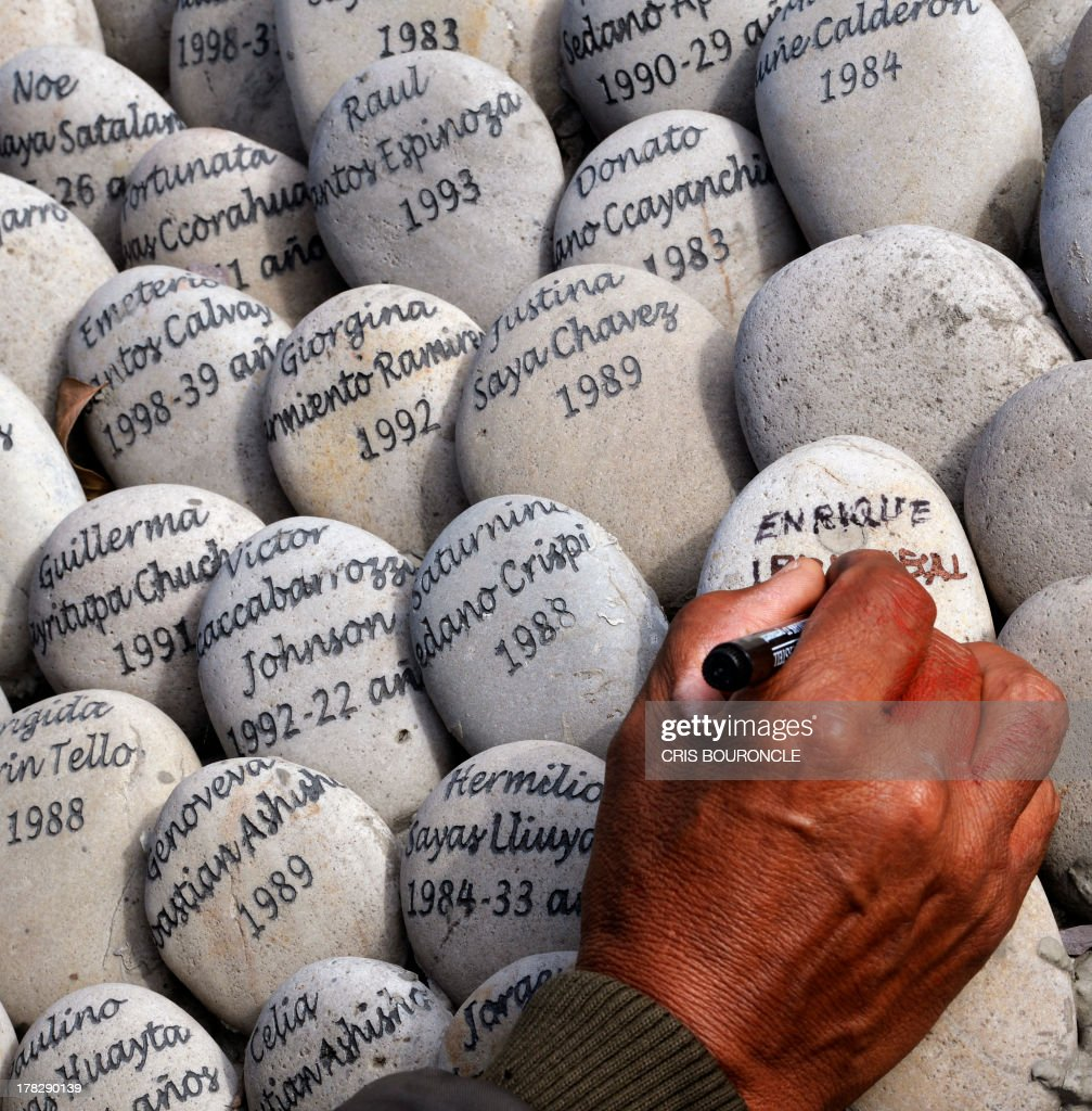 A man writes the name of his father at a symbolic graveyard of stones reading names of victims of the war against terrorist groups as The Shinning Path and the Tupac Amarus during the 80's and 90's, in Lima on August 28, 2013. Relatives of victims commemorate the 10th anniversary of the release of the report of the Commission of Truth and Reconciliation of Peru, which concluded that there were 69.000 people killed or missing during the 80's and 90's.