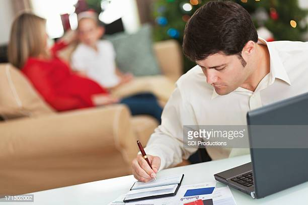 Man writing checks trying to pay Christmas bills