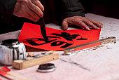 man writing Chinese calligraphy