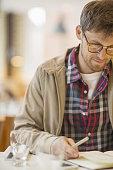 Man writing in cafe