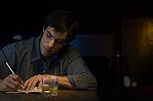 Man writing in notebook, sitting in bar