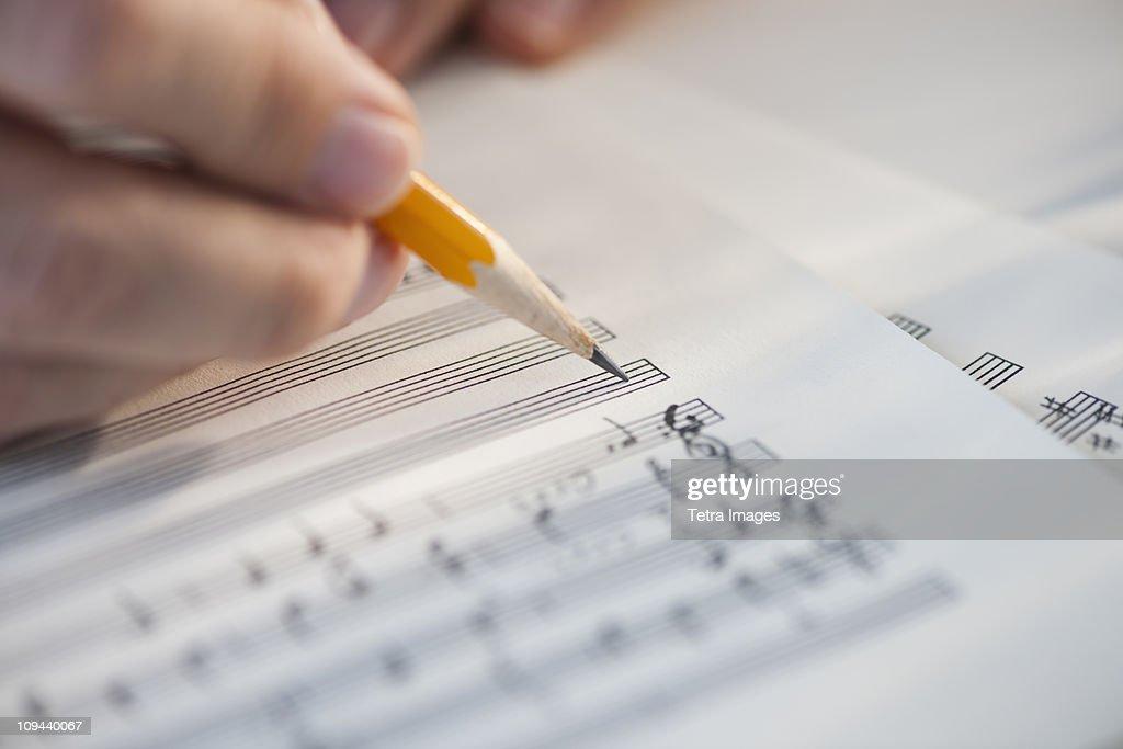 Man writing notes on sheet music : Stock Photo