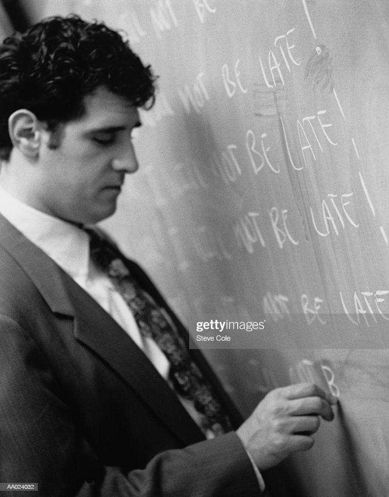 Man Writing on a Chalkboard