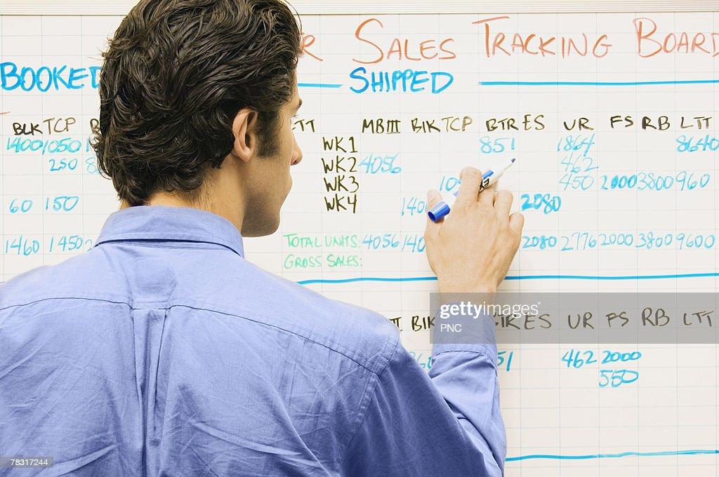 Man writing on dry erase board : Stock Photo