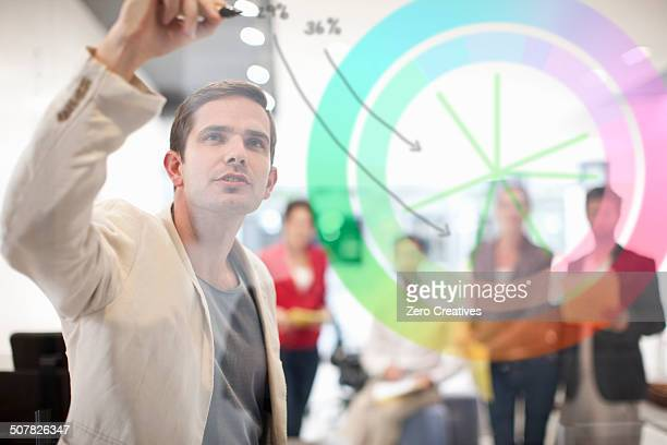 Man writing on glass screen, colleagues watching