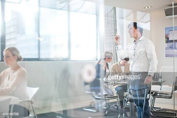 Man writing on glass wall, colleagues in background