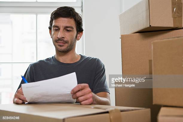 Man Writing on Shipping Invoice