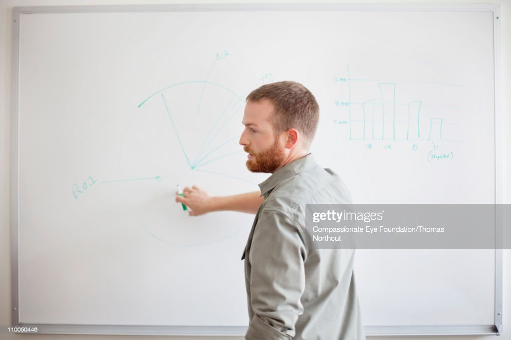 Man writing on white board with green marker : Foto de stock