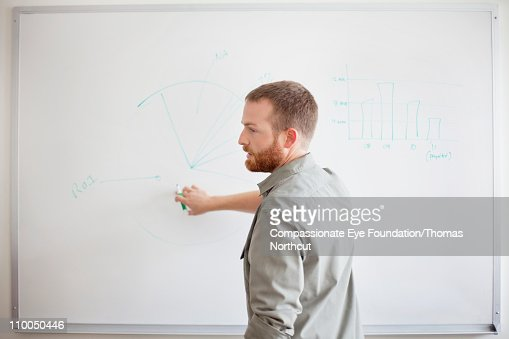 Man writing on white board with green marker : Stock Photo