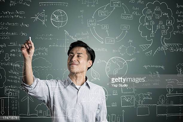 Man writting a formula in chalk on a blackboard