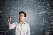 Man wrote a formula in chalk on a blackboard