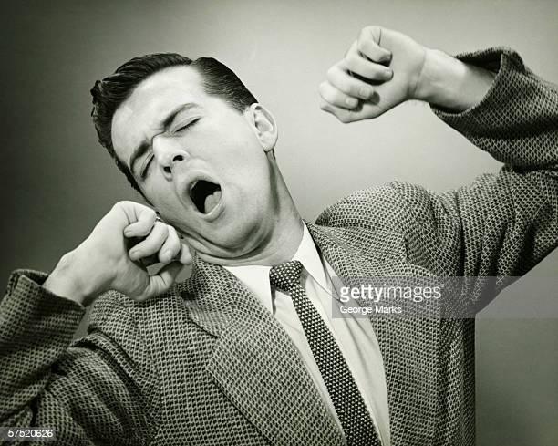 Man yawning and stretching in studio, (B&W),