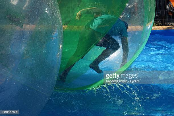 Man Zorbing On Swimming Pool