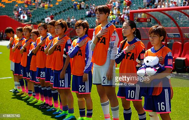 Mana Iwabuchi of Japan holds a bear wearing a shirt in honor of Kozue Ando who broke her leg in an earlier match as they stand for their National...