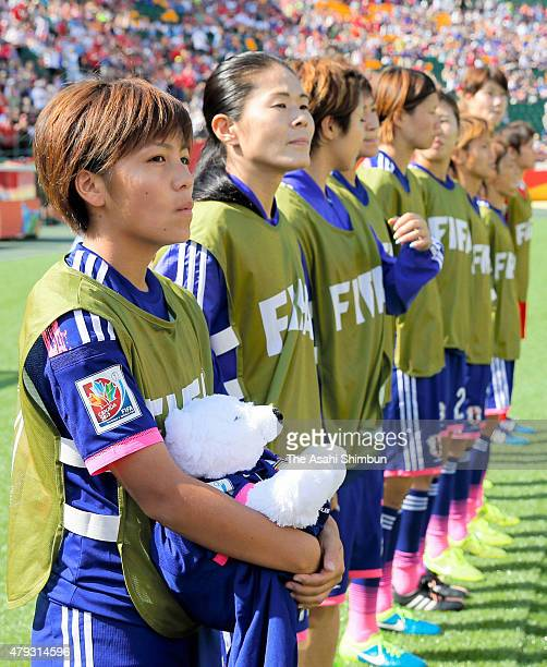 Mana Iwabuchi of Japan holds a teddy bear wearing the shirt of Kozue Ando lines up for the national anthem at the bench prior to the FIFA Women's...