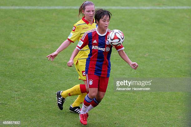 Mana Iwabuchi of Muenchen battles for the ball with Emily Evels of Hoffenheim during the Allianz FrauenBundesliga match between FC Bayern Muenchen...