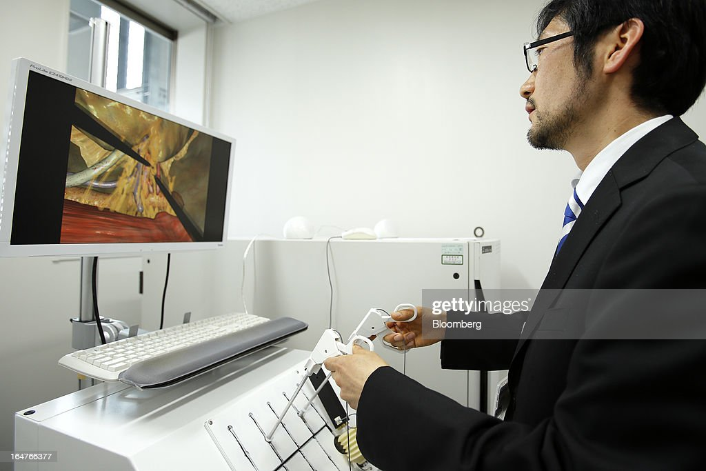 Manabu Nagasaka, researcher of the research and development department at Mitsubishi Precision Co., demonstrates the Lap-Pass, a laparoscopic surgery simulator for doctors to practice surgical operations on three-dimensional computer graphics (CG) images from patients' data obtained by CT or MRI, at Yokohama City University's (YCU) Advanced Medical Research Center (AMRC) in Yokohama City, Kanagawa Prefecture, Japan, on Monday, March 18, 2013. Japan aims to be a nation with the most advanced medical technologies and healthcare services in the world and to develop the medical industries for the revitalization of the country's economy. Photographer: Kiyoshi Ota/Bloomberg via Getty Images