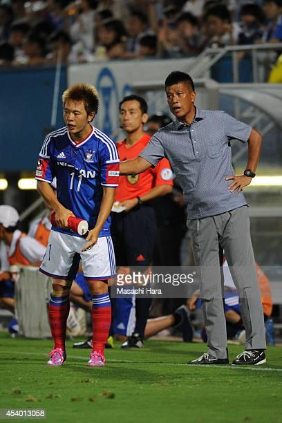 Manabu Saito and Yasuhiro Higuchicoach of Yokohama FMarinos look on during the J League match between Yokohama FMarinos and Kawasaki Frontale at...