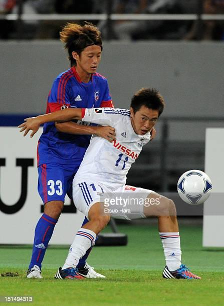 Manabu Saito of Yokohama FMarinos and Kenta Mukuhara of FC Tokyo compete for the ball during the JLeague match between FC Tokyo and Yokohama FMarinos...