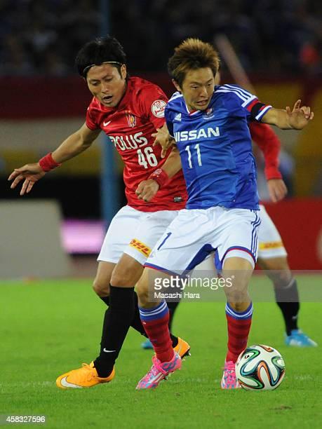 Manabu Saito of Yokohama FMarinos and Ryota Moriwaki of Urawa Red Diamonds compete for the ball during the JLeague match between Yokohama FMarinos...