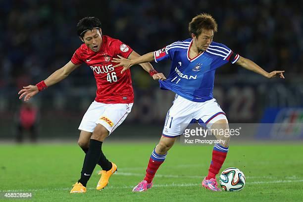 Manabu Saito of Yokohama FMarinos and Ryota Moriwaki of Urawa Reds compete for the ball during the JLeague match between Yokohama FMarinos and Urawa...